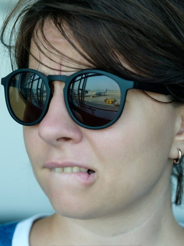 Frau blickt mit Flugangst aus dem Fenster auf ein Flugzeug